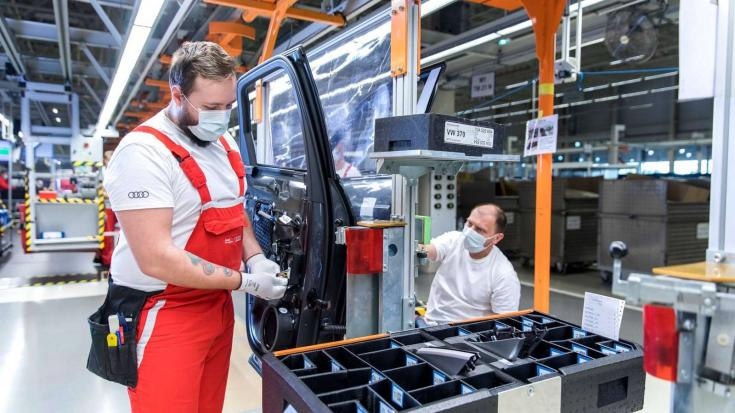 Munkások dolgoznak szájmaszkban a győri Audi-gyárban
