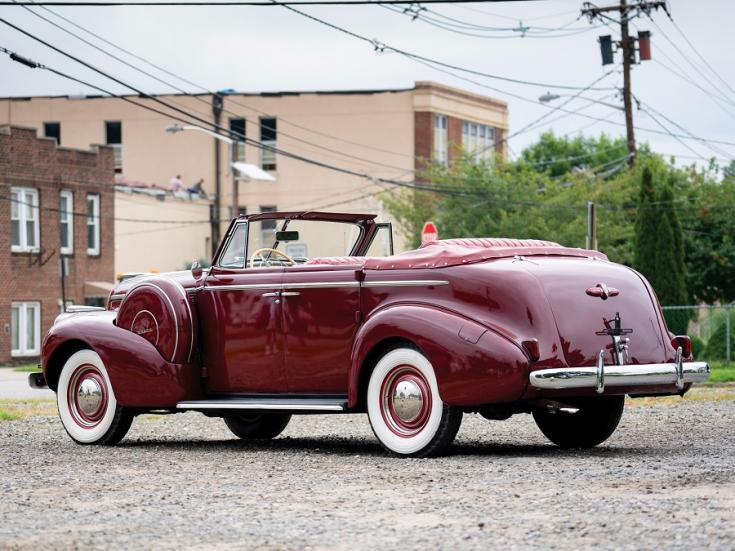 1940 Buick Special Sport Phaeton, meggyvörös kabrió limuzin, hátulnézet, oldalnézet, balról, alulról fotózva, háttérben fák és téglaházak