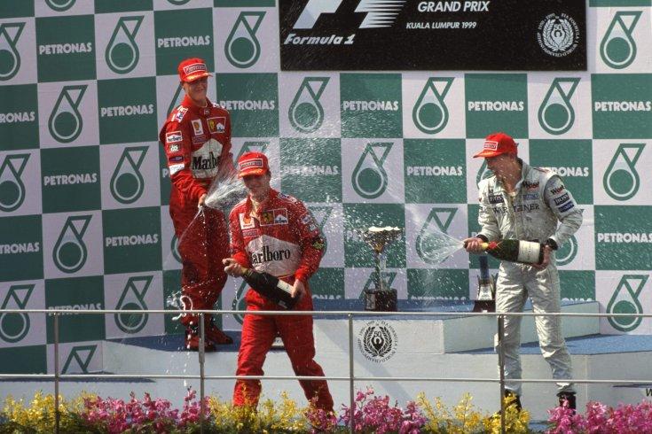 Irvine, Häkkinen és Schumacher pezsgőzik az 1999-es Maláj Nagydíj dobogóján