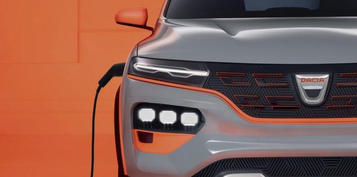 Új Dacia Spring elektromos autó, töltővel az oldalán, elölről