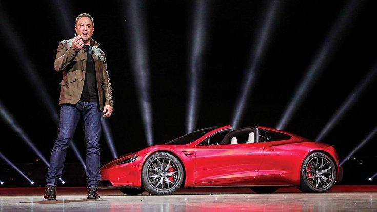 Elon Musk a színpadon magyaráz, háttérben új Tesla Roadsterrel