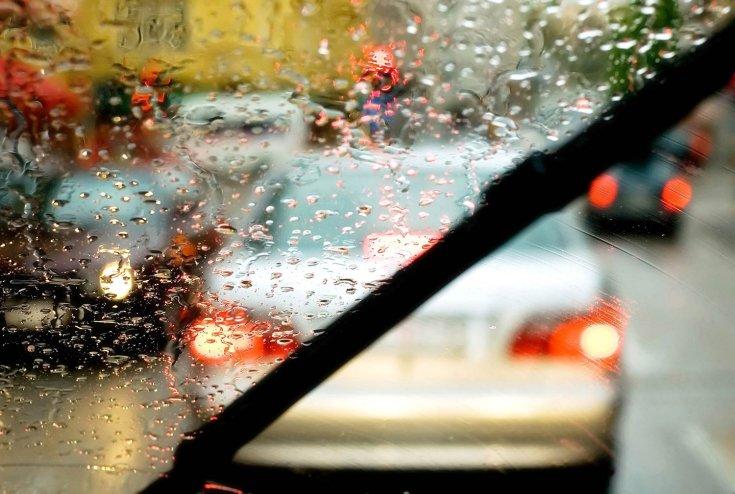 Esős szélvédőt takarító ablaktörlő lapátok egy autó utasteréből nézve