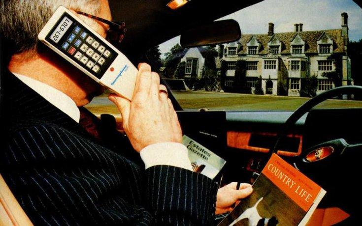 Jaguárban autós telefonon beszélő üzletember