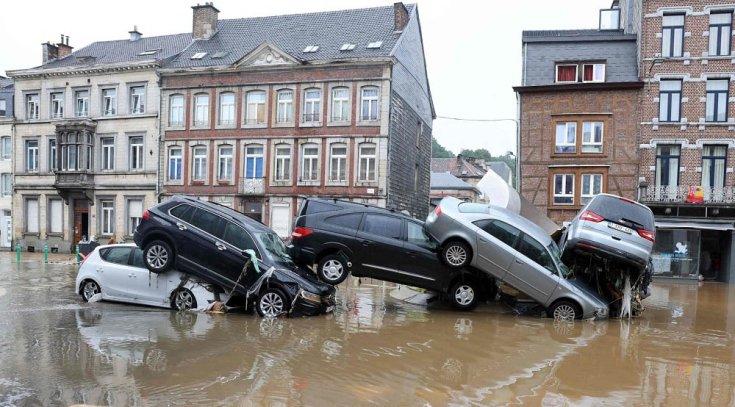 árvíz által egymásra pakolt, összetört autók