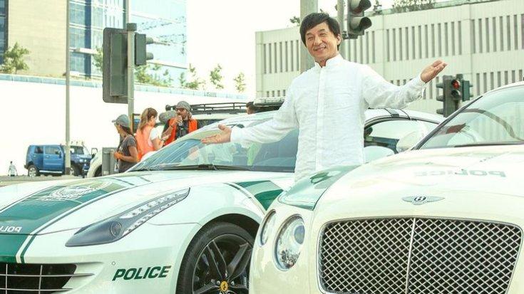 Jackie Chan két autó között áll