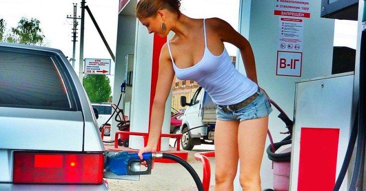 Lenge öltözetű lány tankol a benzinkúton