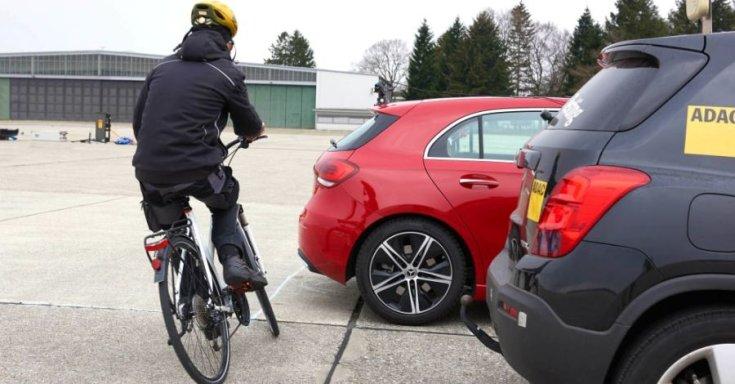 Kerékpáros az ADAC tesztautója mögött