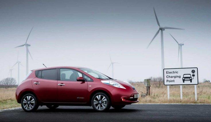 Nissan Leaf oldalról, a háttérben szélerőművek