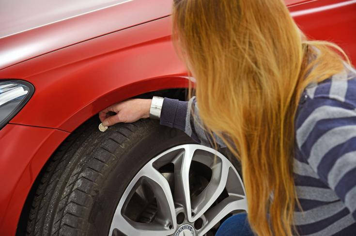 Gumiabroncs profilmélységét ellenőrzi egy női sofőr