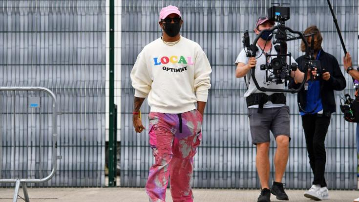 Lewis Hamilton érdekes ruhában kamerás emberek mellett