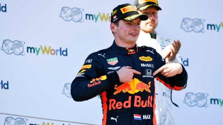 Max Verstappen egy győzelem után a Honda emblémára mutat. háttérben Bottas