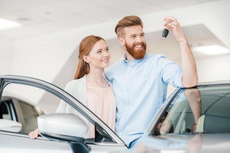 autó kulcsát néző férfi egy nő társaságában