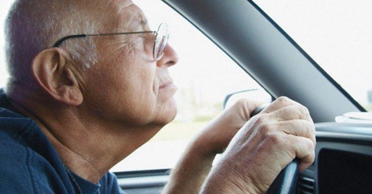 Idős sofőr fogja két kézzel a kormányt