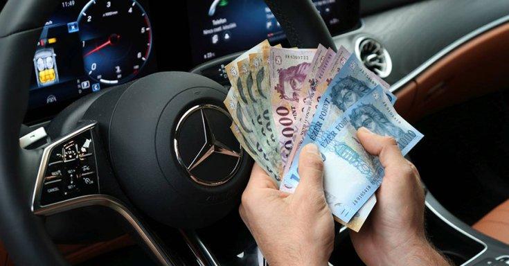 kéz egy köteg pénzt tart egy autó kormánya előtt