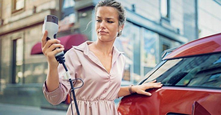 fiatal hölgy tanácstalanul nézegeti a villanyautó töltőjét