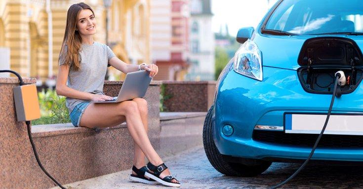 Elektromos autót töltő nő