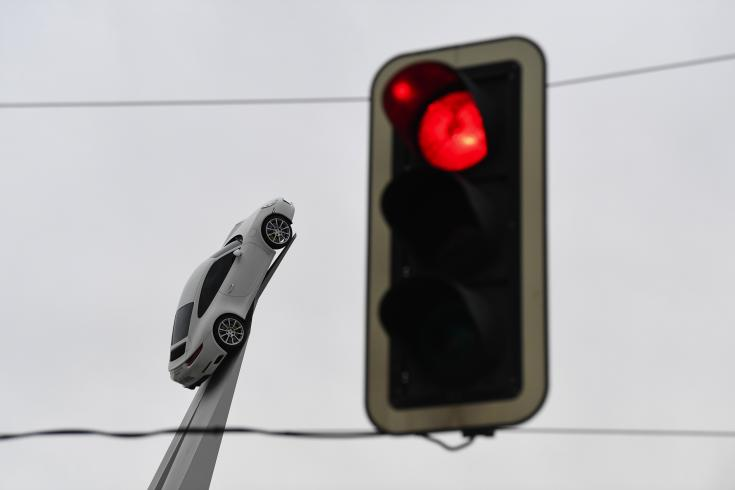 Porsche autó az előtérben egy pirosan világító közlekedési lámpával