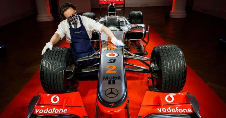 Lewis Hamilton McLaren-Mercedese szemből egy kiállító pódiumon szemből