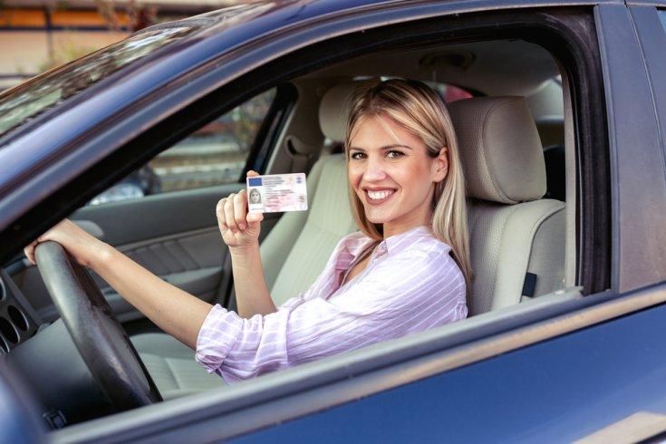nő mosolyog a volánnál, jogosítvánnyal a kezében