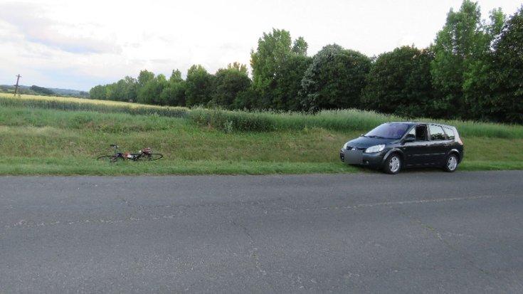 Kerékpár és személygépkocsi az autóút szélén