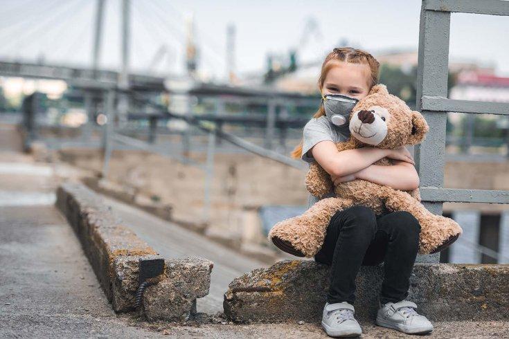 Kislány egy plüssjátékkal ül a padkán