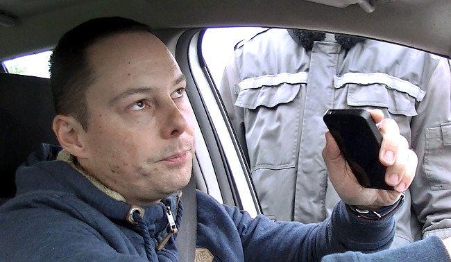 Autóvezető mobillal a kezében, mellette egy rendőr