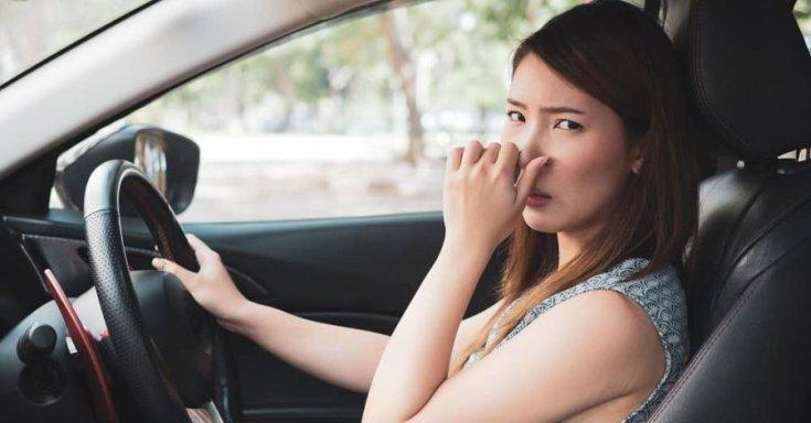 orrát fogó, autót vezető nő