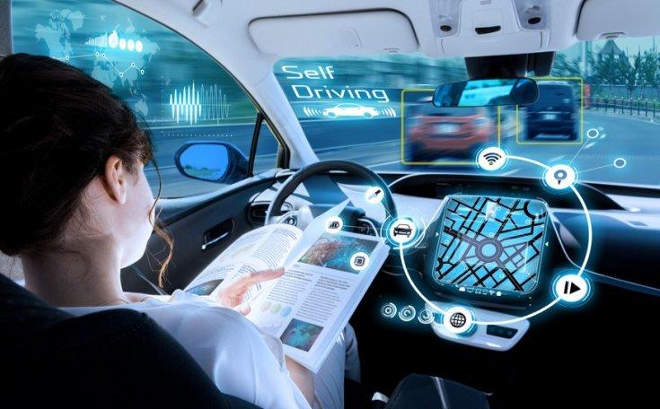 Önvezető autóban újságot olvas egy nő anélkül, hogy a vezetésre koncentrálna