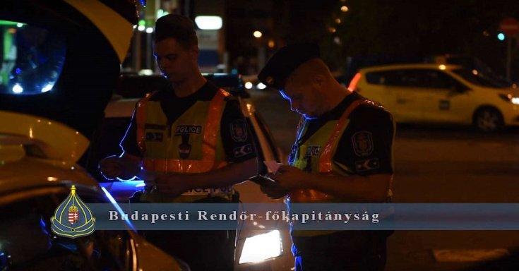 Rendőrök ellenőriznek egy autót a budapesti éjszakában