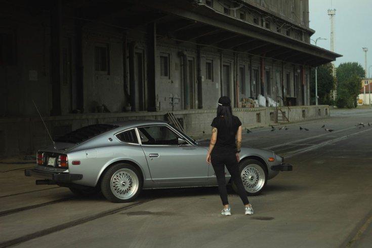 Rupa Adrienn autós újságíró Datsun S30 modell előtt állva, háttal