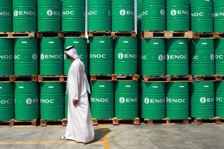 arab férfi sétál olajoshordók előtt