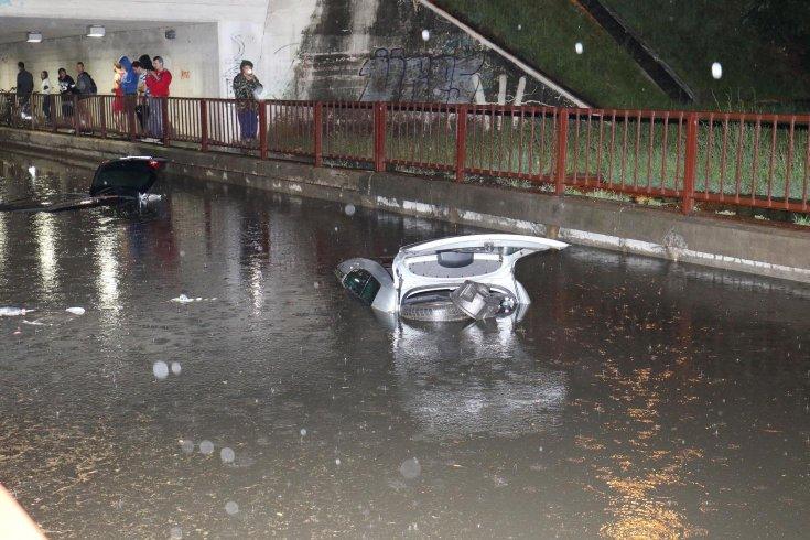 bámészkodók nézik a víz alá merült szolnoki autókat