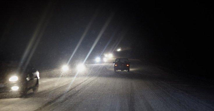 Autók havas úton, sötétben közlekednek