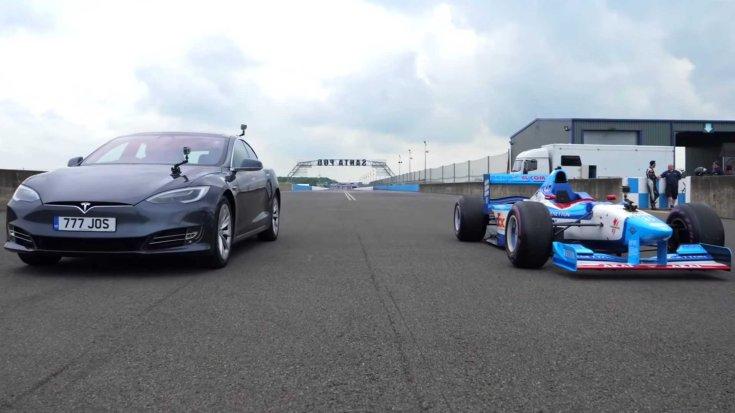 Tesla Model S és Benetton Forma-1-es autó egymás mellett, szemből