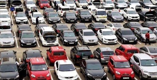 Használtautók egy hatalmas parkolóban egymás mellett