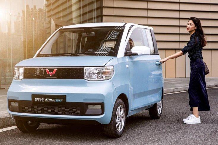 egy hölgy éppen kinyitja a Wuling Hongguang Mini EV ajtaját