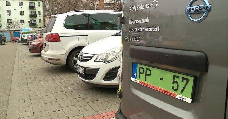 Zöld rendszámos Nissan áll egy helyben egy parkolóban